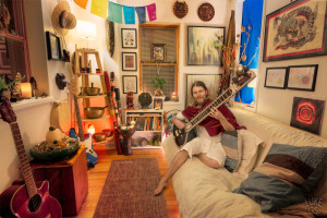 Blair Francis plays a tune on his Sitar surrounded by his sacred objects