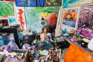 Joe Clarke sits in his paint room, his paintings lining the walls all around him.