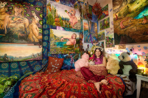 Talented artist Martina sits in bed surrounded with her beautiful paintings.