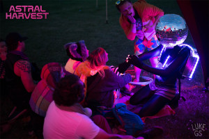 friends gather around a man in a glowing costume at Astral Harvest by Luke GS