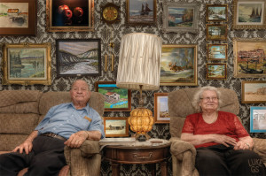 Smith Grandparents backed by a digital composition of all their favorite paintings