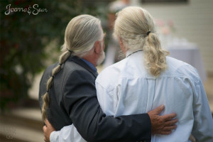 Dad's of bride and groom have matching ponytails!