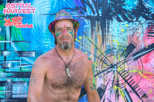 Painter Joe Clarke poses with his painting at Astral Harvest Festival