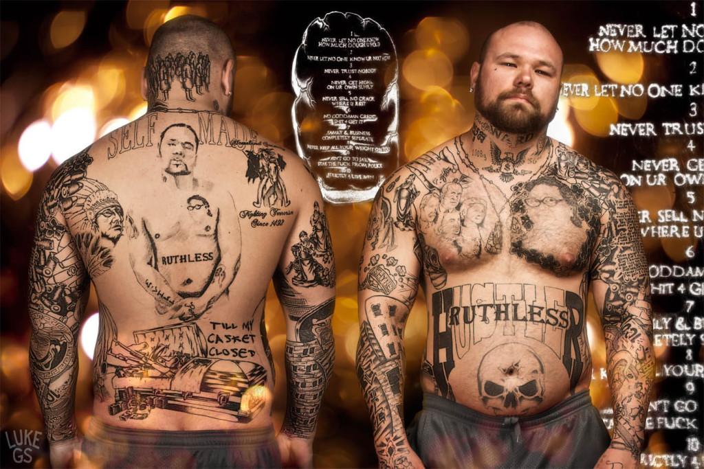 a tattooed thug stands with his tattoos showing